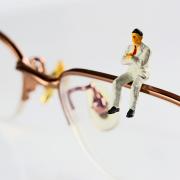 Uomo e occhiali in miniatura.