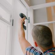 giovane falegname durante l'installazione di un infisso in legno in una casa.