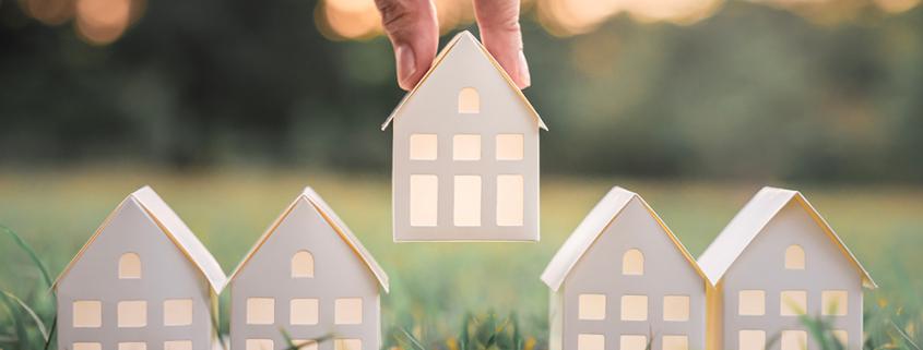 Mano che sceglie modello di casa di carta bianca dal gruppo di casa su erba verde, messa a fuoco selettiva, pianificazione di acquistare proprietà.