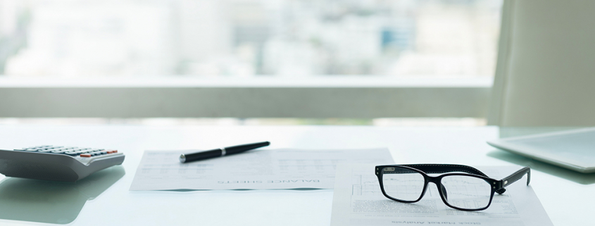 Bicchieri con calcolatrice e notebook su scrivania con vista sulla città. Concetto di contabilità e bilancio.